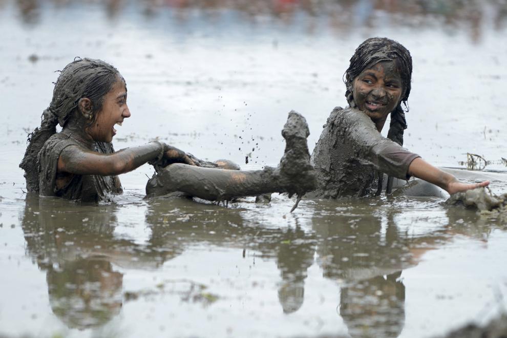 Tinere nepaleze se joacă într-o orezărie din Pokhra, 200 km vest de Kathmandu, sâmbătă, 29 iunie 2013.