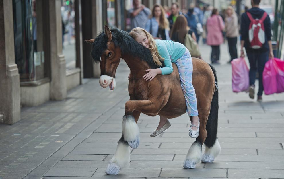 Un copil pozează călare pe un ponei cu ocazia unei şedinţe foto organizate de un magazin de jucării din Londra, joi, 27 iunie 2013.