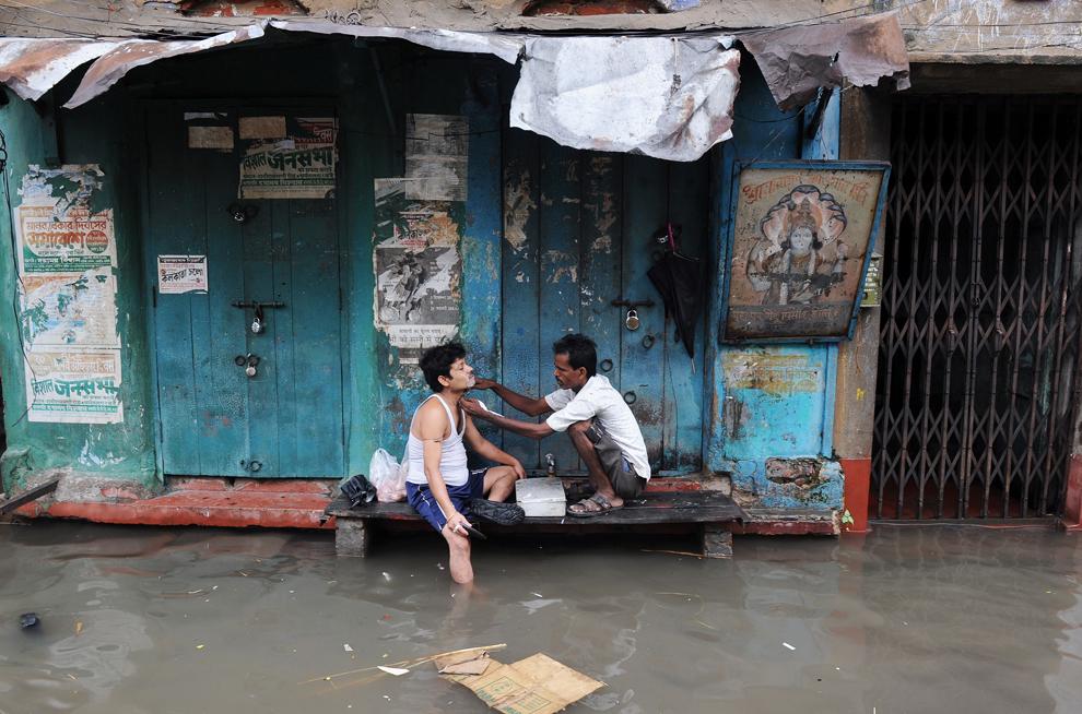 Un bărbier bărbiereşte un client pe marginea unei străzi inundate din Calcuta, India, duminică, 30 iunie 2013.