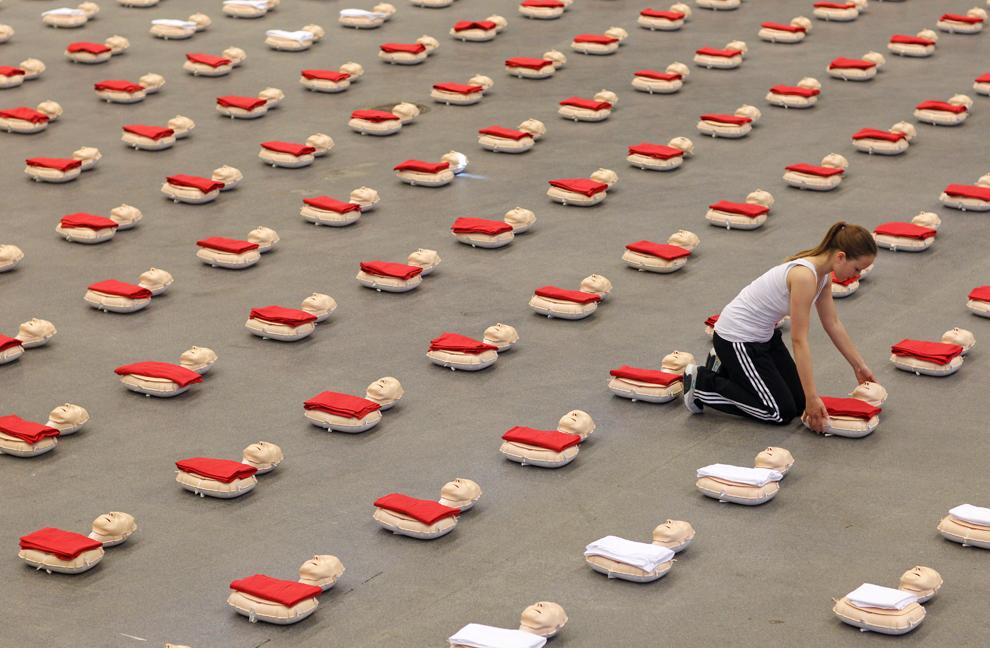 O fată aranjează manechine ce urmează a fi folosite în cadrul unui exerciţiu de reanimare de către 600 de elevi, în Lingen, Germania, marţi, 18 iunie 2013.