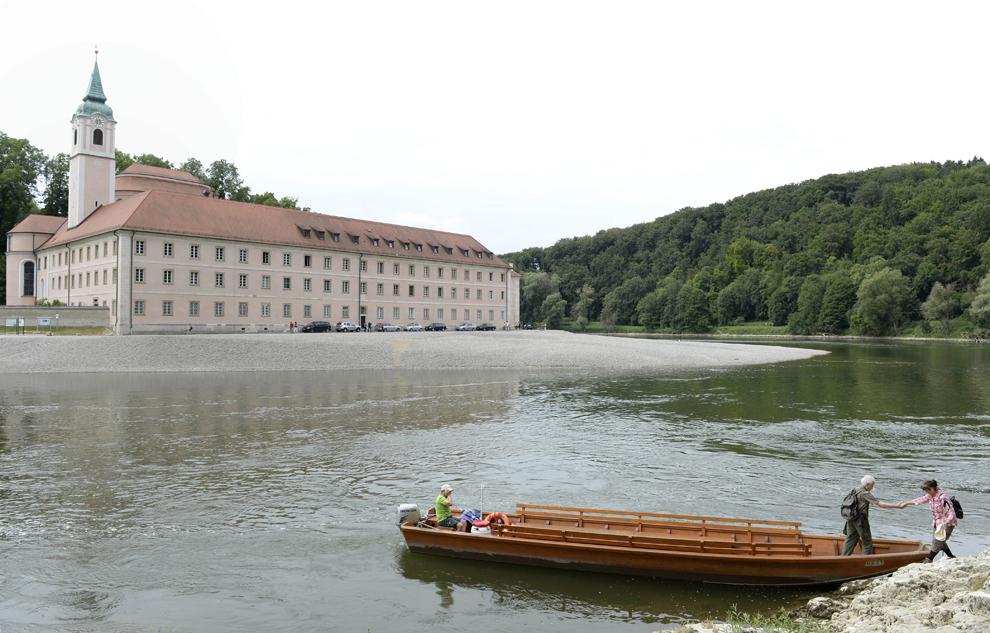 O turistă se urcă într-o barcă pentru a traversa Dunărea şi a ajunge la abaţia Weltenburg, în sudul Germaniei, luni, 29 iulie 2013.