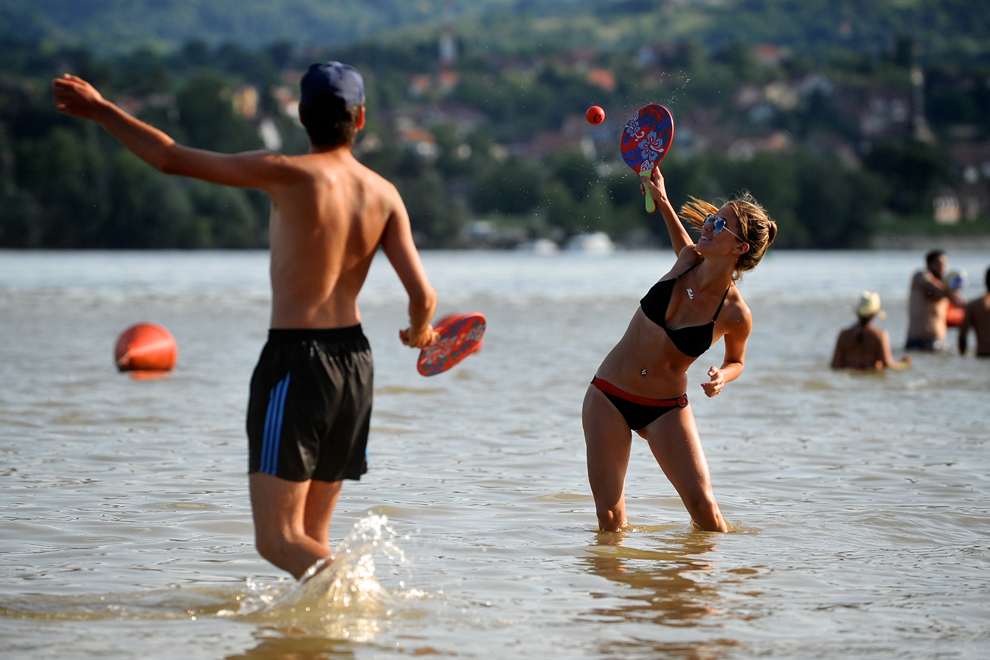 Un cuplu joacă tenis de plajă în fluviul Dunărea, în Novi Sad, Serbia, vineri, 12 iulie, 2013.