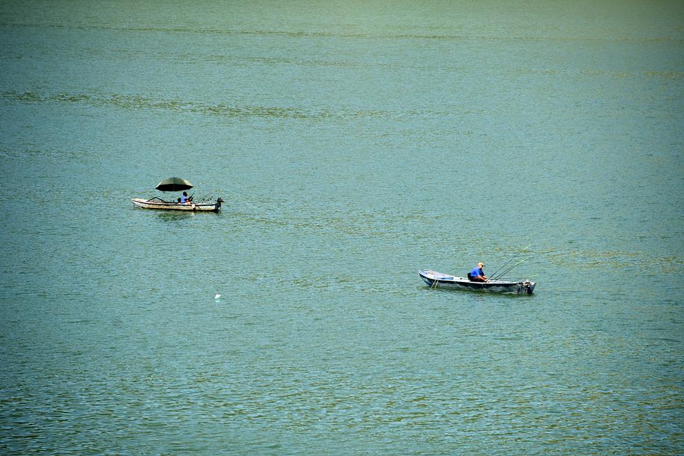 Doi bărbaţi aflaţi în bărci pescuiesc pe fluviul Dunărea, în apropierea oraşului Golubac, Serbia, miercuri, 24 iulie 2013.