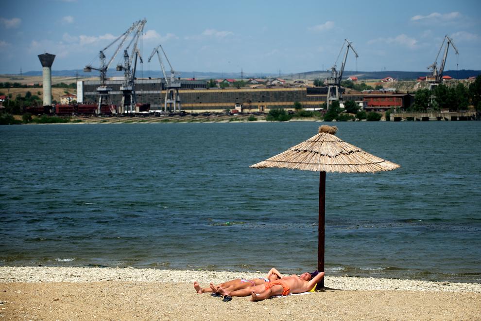 Un cuplu face plajă pe unul din malurile fluviului Dunărea, în Kladovo, Serbia, miercuri, 24 iulie 2013.