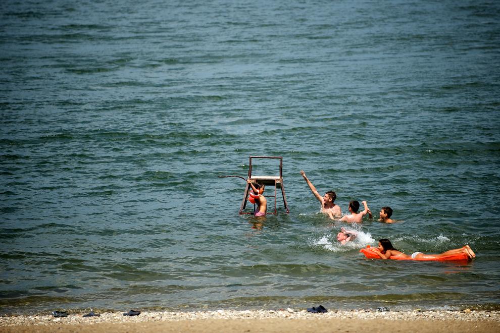 Un grup de copii se jocă în apă, lângă o plajă de pe malul fluviului Dunărea, în Kladovo, Serbia, miercuri, 24 iulie 2013.