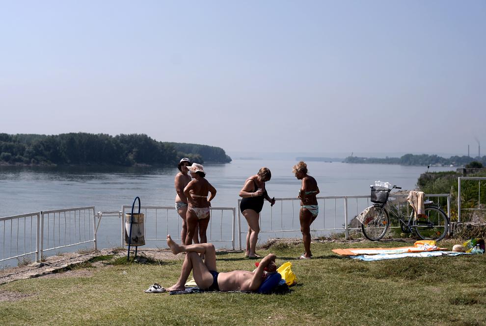 Mai multe persoane fac plaja pe malul fluviului Dunărea, în apropierea oraşul Vidin, Bulgaria, joi, 18 iulie 2013.