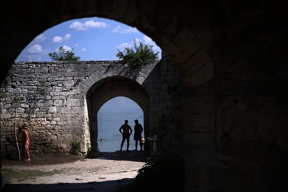 Două persoane stau la intrarea într-o fortăreaţă medievală, aflată pe malul fluviului Dunărea, în apropierea oraşul Vidin, Bulgaria, joi, 18 iulie 2013.