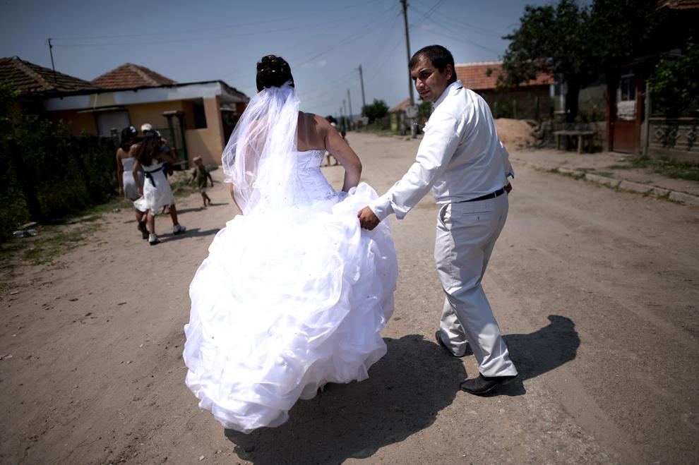 Un cuplu proaspăt însurat se plimbă în satul Dolni Tsibar din apropierea fluviul Dunărea, în Bulgaria, sâmbătă, 20 iulie 2013.