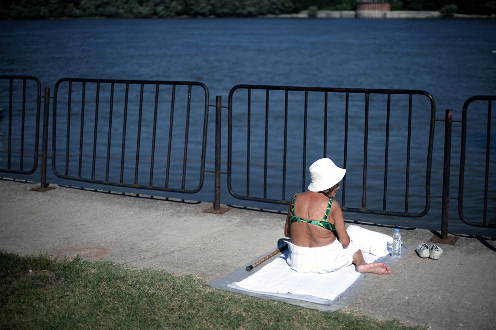 O femeie face plajă pe malul bulgăresc al Dunării, în apropierea portului Ruse din Bulgaria, luni, 22 iulie 2013.