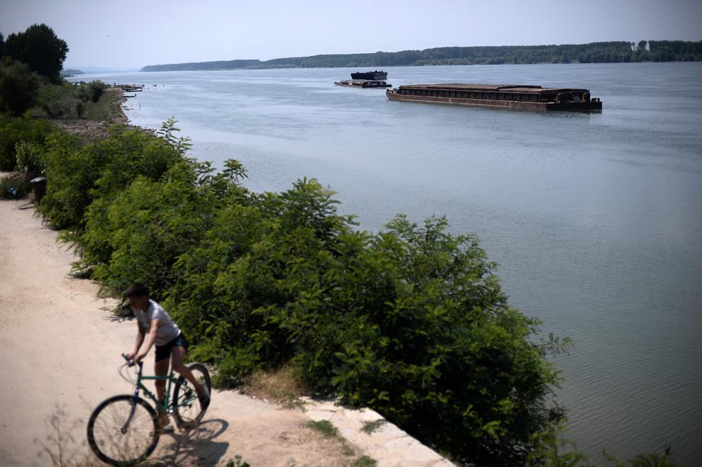 Un băiat se plimbă cu bicicleta pe malul bulgăresc al Dunării, în apropierea oraşului Lom, joi, 18 iulie 2013.