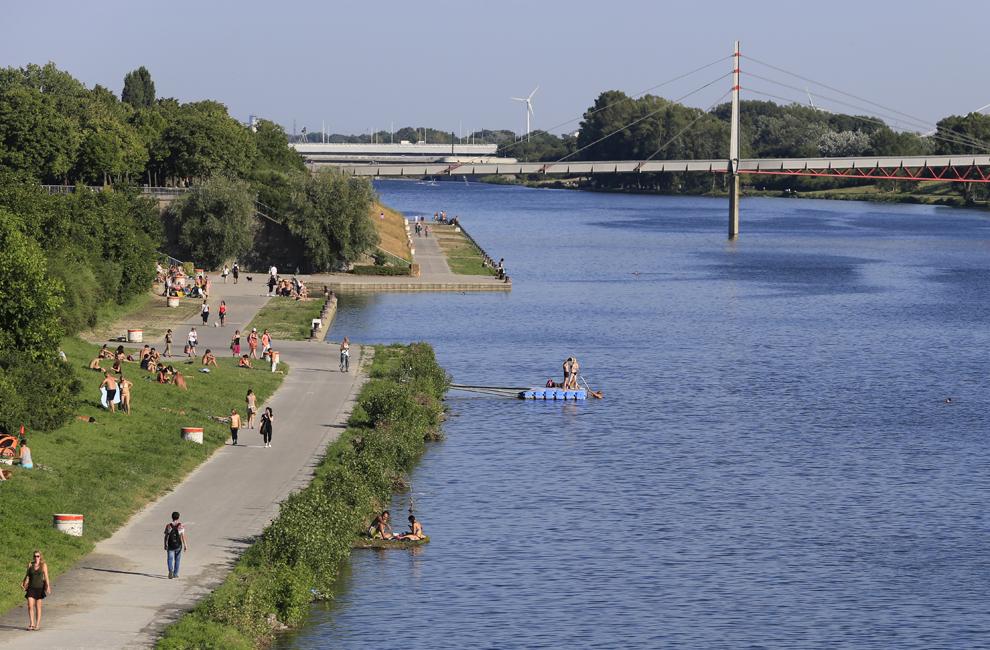 Oamenii se bucură de vremea bună pe malul Dunării, în Viena, marţi, 16 iulie 2013.