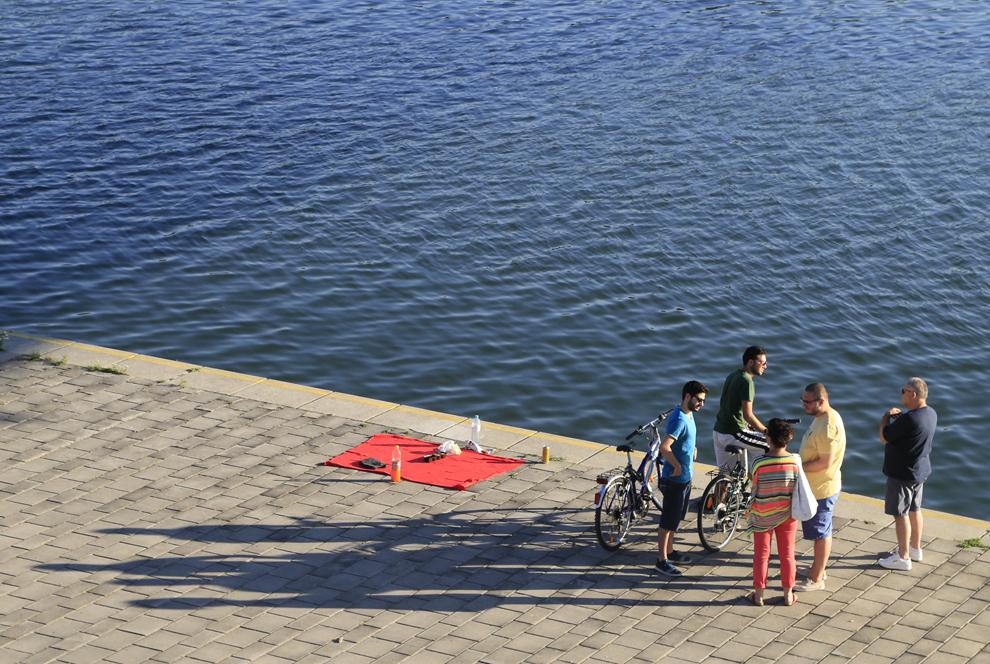 Mai multe persoane se bucură de soare pe malul Dunării, în Viena, marţi, 16 iulie 2013.