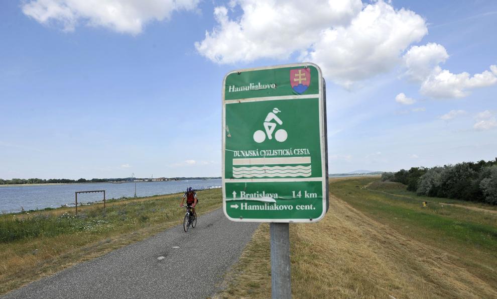 Un bărbat pedalează pe o pistă aflată  pe malul Dunării, în Bratislava, sâmbătă, 20 iulie 2013.
