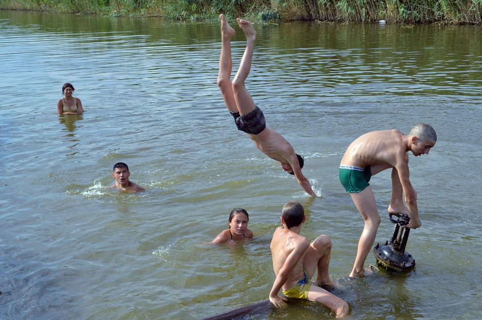 Mai mulţi copii sar în apă şi înoată într-unul din braţele Dunării, în oraşul ucrainean Izmail, în regiunea Odessa, miercuri, 10 iulie 2013.
