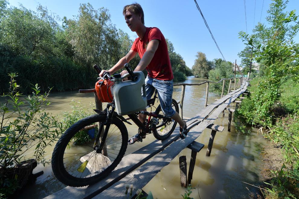 Un bărbat traversează pe bicicletă un podeţ în micul oraş Vylkove, cunoscut şi ca 'Veneţia Ucrainei', în regiunea Odessa, joi, 11 iulie 2013. Oraşul este ultima aşezare aflată pe malurile Dunării înaintea vărsării fluviului în mare.