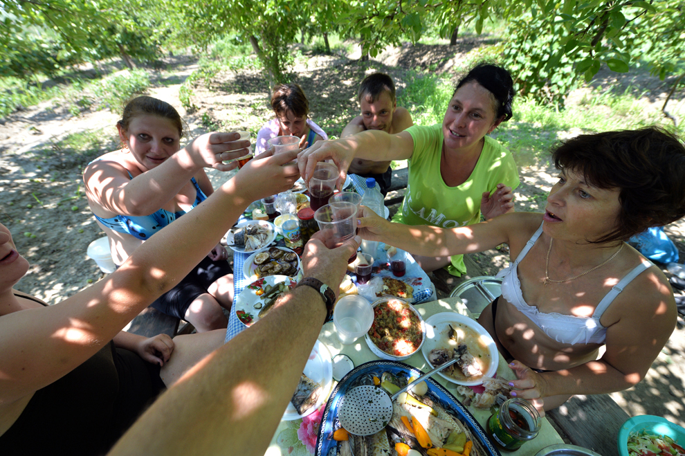 Un grup de persoane toastează cu vin de casă în timpul unei mese festive, în apropierea fluviul Dunărea, în oraşul Vylkove din regiunea Odessa, Ucraina, joi, 11 iulie 2013.