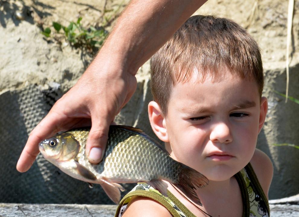 Un băiat se uită la peştele prins de mama sa, în oraşul Vylkove din regiunea Odessa, Ucraina, joi, 11 iulie 2013.