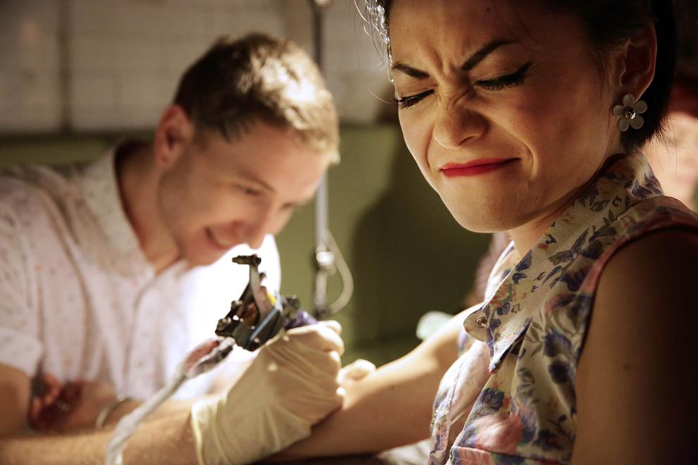 O femeie este tatuată gratis în timpul festivalului Dirty Boogie Rockabilly, după ce, prin rotirea 'Roţii durerii', a ales aleator un model, în Hong Kong, sâmbătă, 20 iulie 2013.