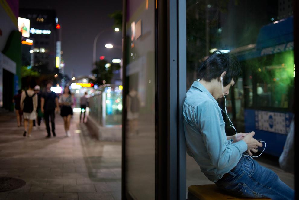 Un bărbat aşteaptă autobuzul cu căştile în urechi, pe o stradă din cartierul Gangnam al Seulului, vineri, 5 iulie 2013.