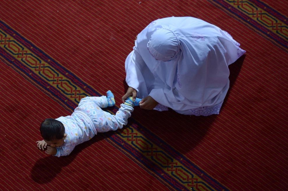 O femeie musulmană indoneziană se întinde spre un copil în timpul rugăciunilor din prima noapte a Ramadanului, la moscheea Istiqlal din Jakarta, marţi, 9 iulie 2013.