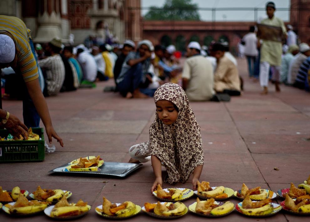 O fetiţă musulmană indiană aranjează farfuriile cu mâncare, înainte de Iftar, la sfârşitul primei zile a Ramadanului, la moscheea Jama Masjid, în New Delhi, joi, 11 iulie 2013.