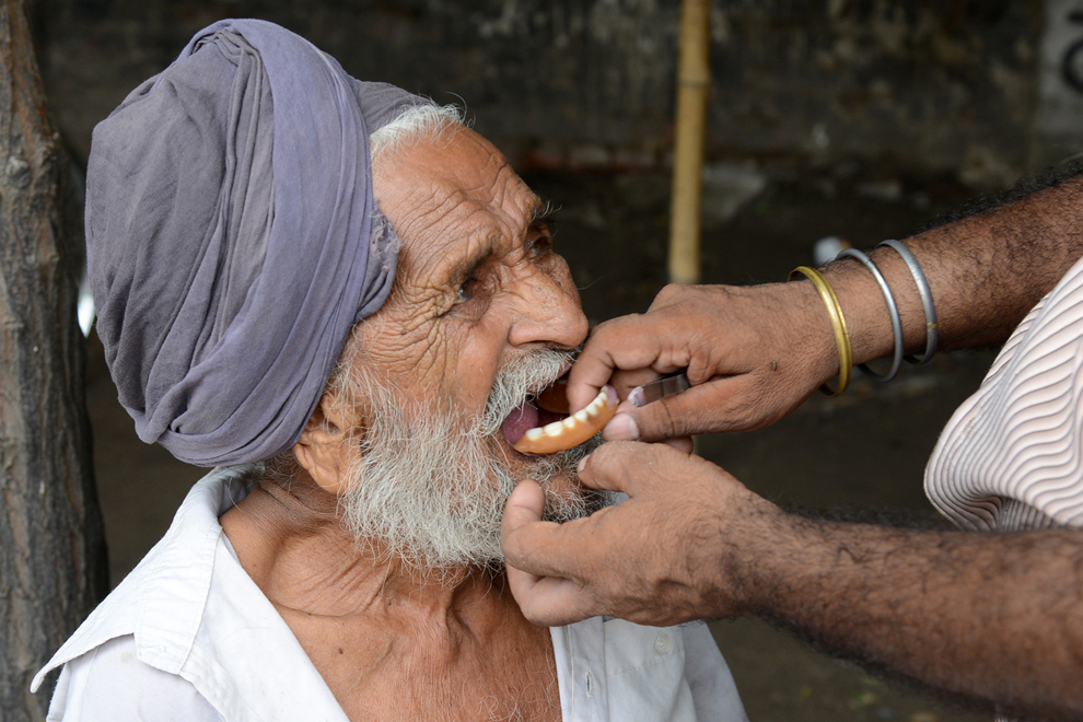 Dentistul indian stradal Kulwant Singh îi instalează pacientului Jagar Singh o proteză, la standul său aflat la marginea drumului, în Amritsar, marţi, 16 iulie 2013. Dentiştii stradali, mulţi dintre ei fără vreo pregătire formală, îşi dobândesc abilităţile ca asistenţi sau tehnicieni dentari şi câştigă între 300 şi 400 de rupii pe zi (5 – 6,70 dolari).
