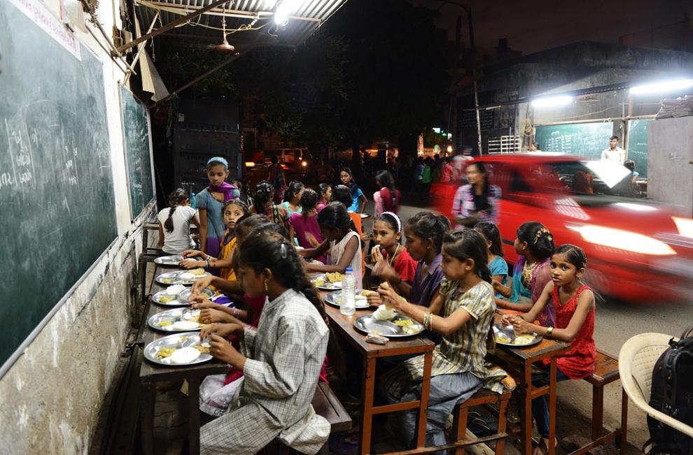 Elevi indieni aparţinând şcolii Footpath din Ahmedabad mănâncă seara târziu, sâmbătă, 20 iulie 2013. Şcoala Footpath a fost iniţiată de Kamalbhai Parmar, proprietarul unei afaceri în domeniul prelucrării metalelor, pentru copiii muncitorilor săi, a celor care reciclează gunoaiele şi a servitorilor, astfel încât aceştia să primească educaţie suplimentară şi o masă gratuită.