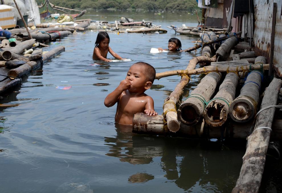 Copii se joacă în apele poluate al golfului Manila, în Manila, marţi, 23 iulie 2013.