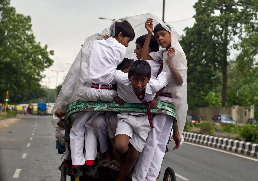 Elevi indieni folosesc o folie de plastic pentru a se proteja de burniţa uşoară, în timp ce se deplasează cu o ciclo-ricşă, în New Delhi, joi, 25 iulie 2013.