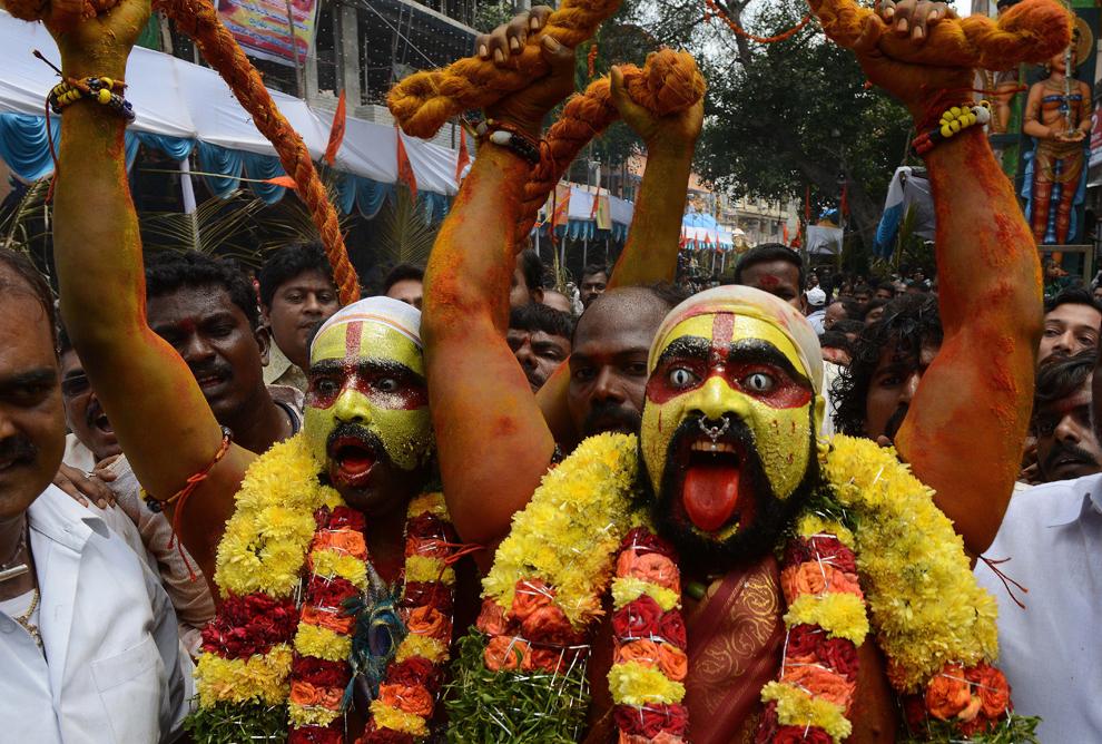 Credincioşi indieni hinduşi, reprezentându-l pe Potharaju, fratele zeiţei Mahankali, dansează pe străzile Secunderabadului, oraşul geamăn al Hyderabadului, în timpul festivalului Bonalu, la templul Sri Ujjaini Mahakali, luni, 29 iulie 2013.