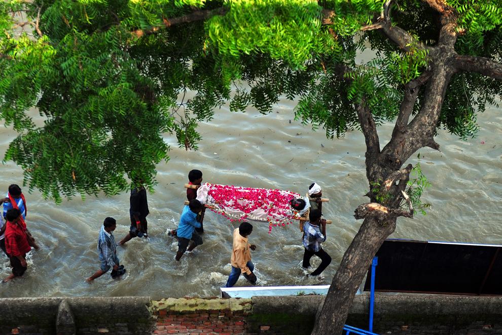 Persoane îndoliate se deplasează cu greu prin apa adusă de inundaţii, în timp ce cară corpul unei persoane decedate, pentru a fi incinerat, în Daraganj Ghat, Allahabad, marţi, 30 iulie 2013.