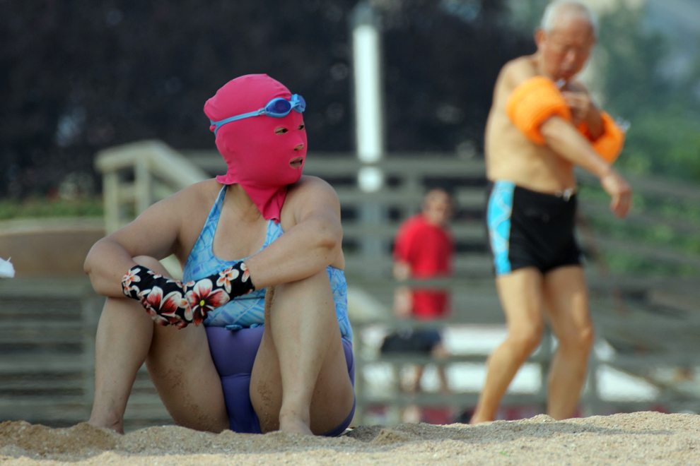 O fotografie realizată miercuri, 3 iulie 2013, înfăţişează o femeie care face plajă purtând un costum de baie şi o mască pentru faţă, denumită 'face-kinis' de către internauţii chinezi, pe o plajă publică din Qingdao, în provincia Shandong din nord-estul Chinei. Măştile pentru faţă au fost create iniţial pentru a proteja împotriva arsurile provocate de expunerea la soare, însă s-au dovedit a fi foarte eficiente şi împotriva insectelor şi meduzelor, mai ales că mulţi chinezi detestă bronzarea, în special pe faţă.