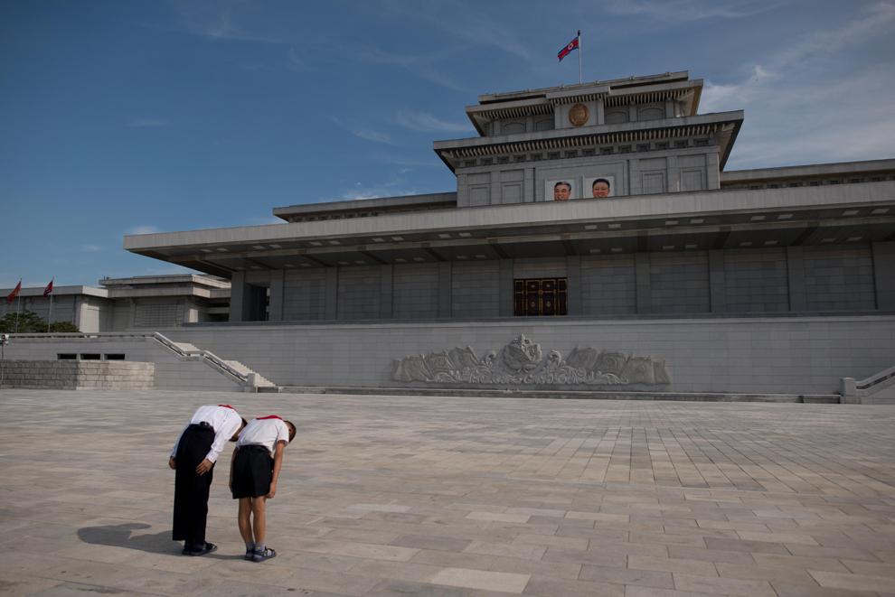 Doi elevi se înclină în faţa portretelor foştilor lideri nord-coreeni, Kim Il-Sung (S) şi Kim Jong-Il (D), în palatul Kumsusan din interiorul mausoleului Sun, în Phenian, joi, 25 iulie 2013.