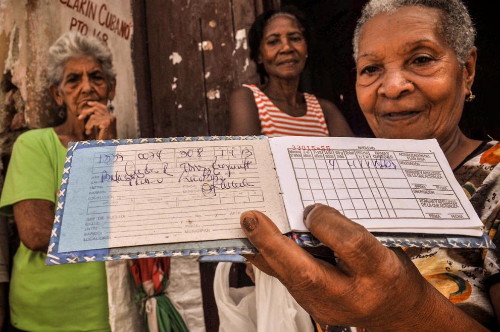 O femeie în vârstă arată fotografului 'libreta', o cartelă cu raţia de alimente de bază, care, din 1963 le-a permis cubanezilor să cumpere alimentele la un preţ mic, puternic subvenţionat, în Santiago de Cuba, miercuri, 10 iulie 2013.