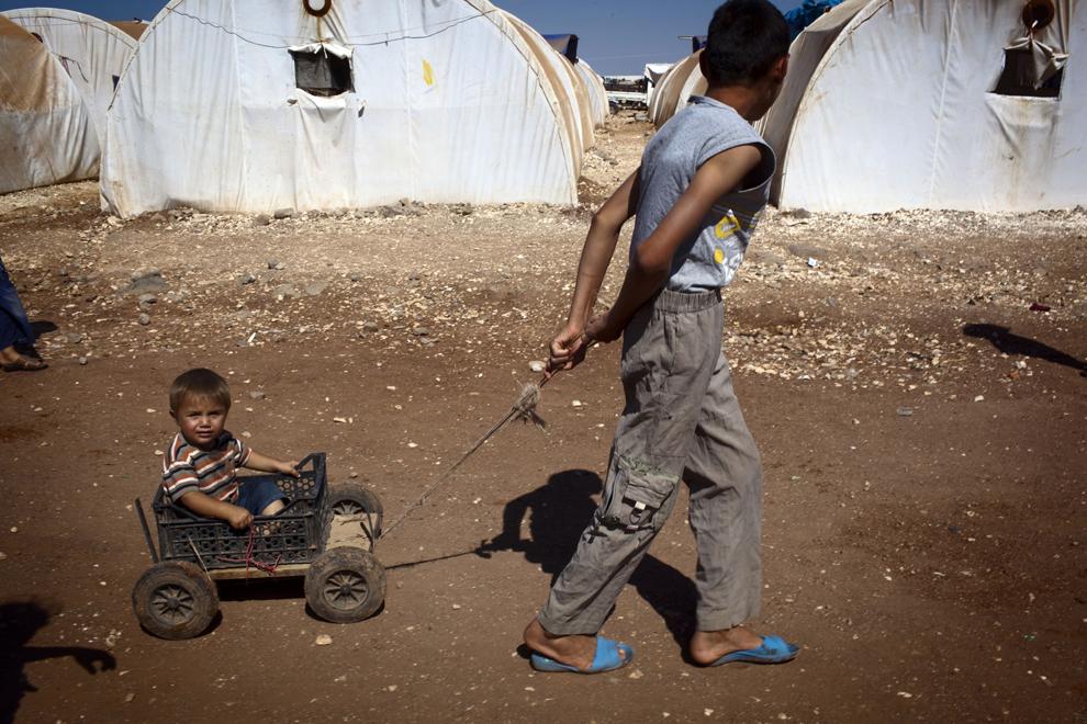 Un băiat sirian trage un cărucior în care se află fratele său mai mic, în tabăra de refugiaţi sirieni Bab al-Salam, aflată în apropierea graniţei cu Turcia, marţi, 2 iulie 2013.