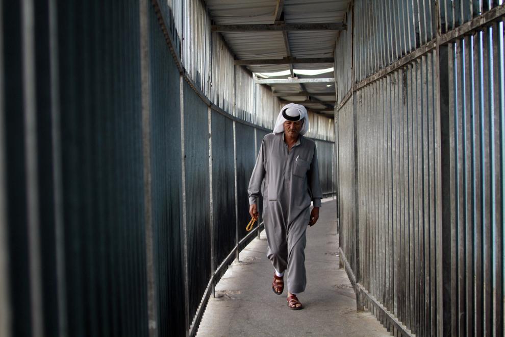Un musulman palestinian trece printr-un punct de control israelian aflat de-a lungul controversatului zid, la periferia oraşului Bethlehem din Cisiordania, în drum spre Ierusalim, unde urmează a participa la rugăciunile ţinute în moscheea Al-Aqsa, în timpul Ramadanului, vineri, 12 iulie 2013.