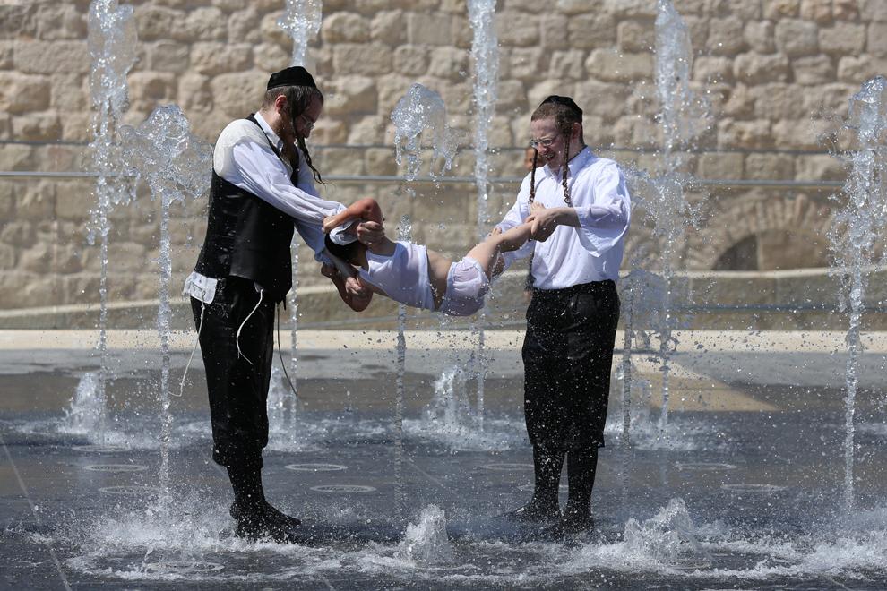Evrei ultra-ortodocşi se răcoresc într-o fântână din Ierusalim, în apropierea zidurilor Oraşului Vechi, marţi, 23 iulie 2013.