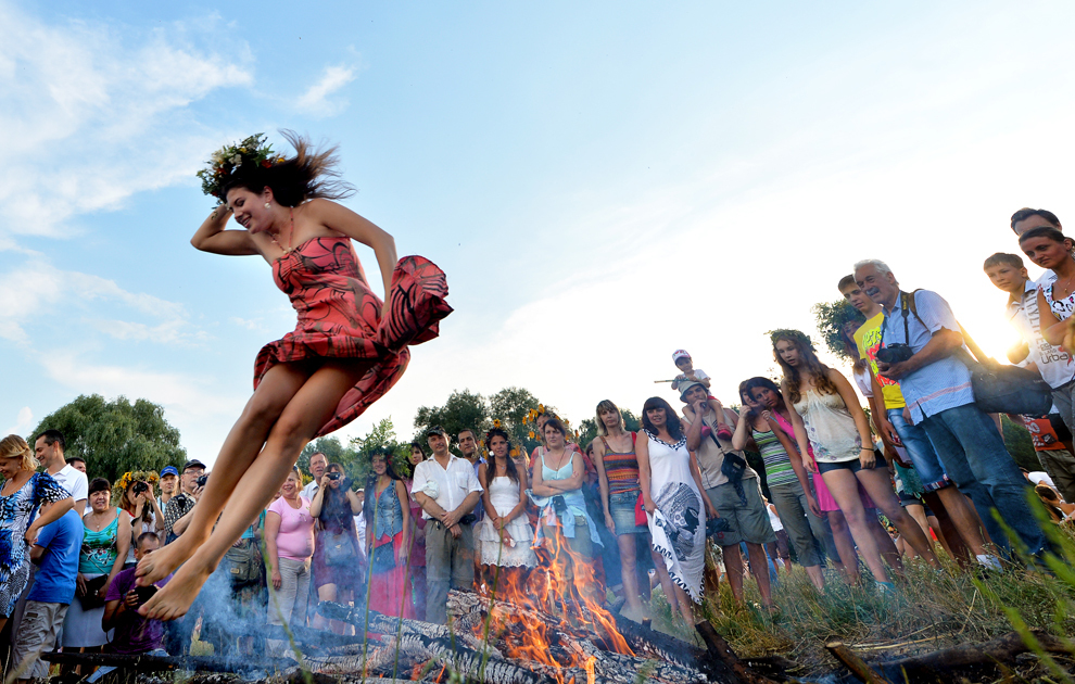 O tânără sare peste un foc de tabără în timpul sărbătorii Nopţii lui Ivan Kupala, o sărbătoare tradiţională slavă cu rădăcini păgâne, în apropierea Kievului, sâmbătă, 6 iulie 2013.