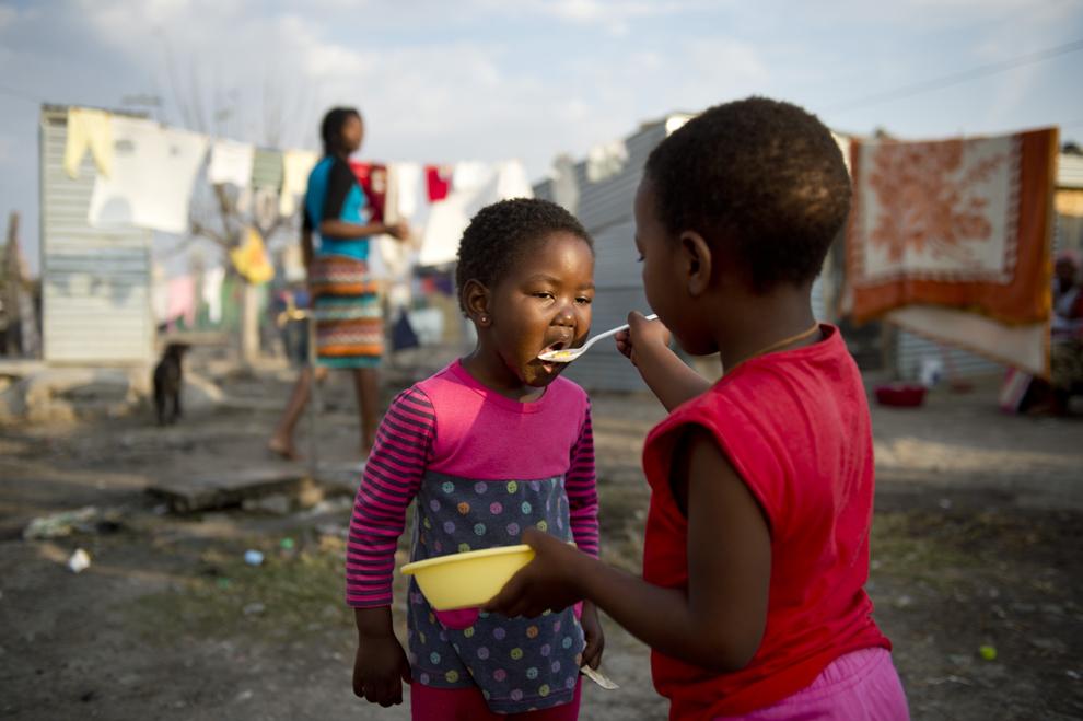 O fetiţă îşi hrăneşte sora, în mahalaua Nkaneng din apropierea minei de platină condusă de compania britanică Lonmin, în Marikana, Africa de Sud, marţi, 9 iulie 2013. Pe 16 august 2012 poliţia minei Marikana a deshis focul asupra minerilor aflaţi în grevă, ucigând 34 şi rănind 78 de grevişti. Minerii continuă să trăiască în condiţii precare, în ciuda unei mici creşteri salariale.