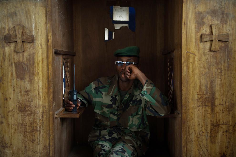 Un soldat al grupării rebele M23 stă într-un confesional, într-o biserică folosită pentru a-i învăţa pe reprezentanţii comunităţilor locale valorile mişcării, la o academie militară din Rumangabo, în teritoriu deţinut de rebeli în estul Republicii Democrate Congo, sâmbătă, 20 iulie 2013.