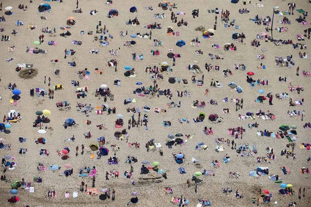 O fotografie aeriană realizată duminică, 21 iulie 2013, înfăţişează oameni stând la soare pe o plajă aglomerată din Scheveningen, Olanda, în timpul unei zile călduroase de vară.
