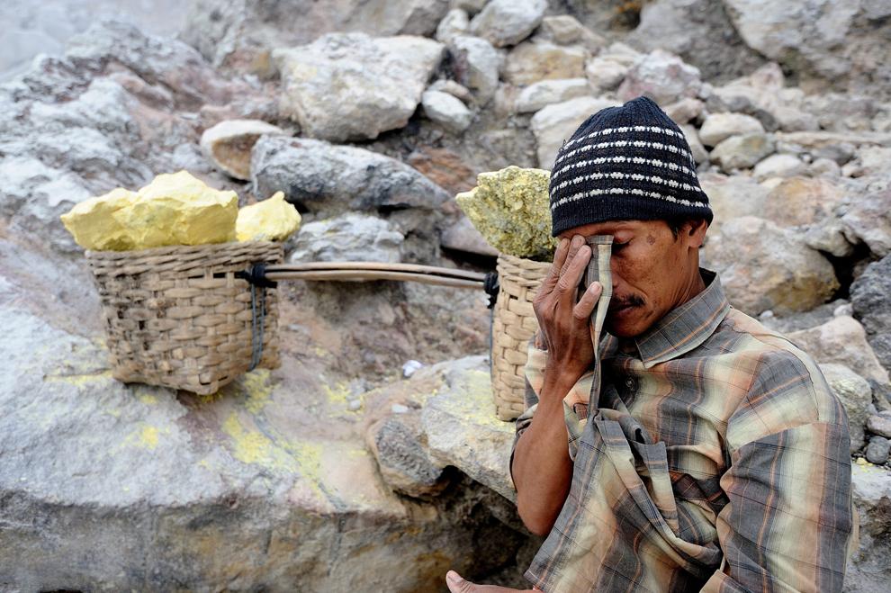 Un miner care lucrează într-o mină de sulf se odihneşte în timp ce cară două coşuri cu sulf, în Arjuna, Java, Indonezia, marţi, 9 iulie 2013. Minerii desprind bucăţile de sulf din craterul vulcanului Ijen cu răngi de metal şi apoi cară încărcăturile, care cântăresc între 50 şi 90 de kg,  pe o distantă de 3 km, până la punctul de cântărire.