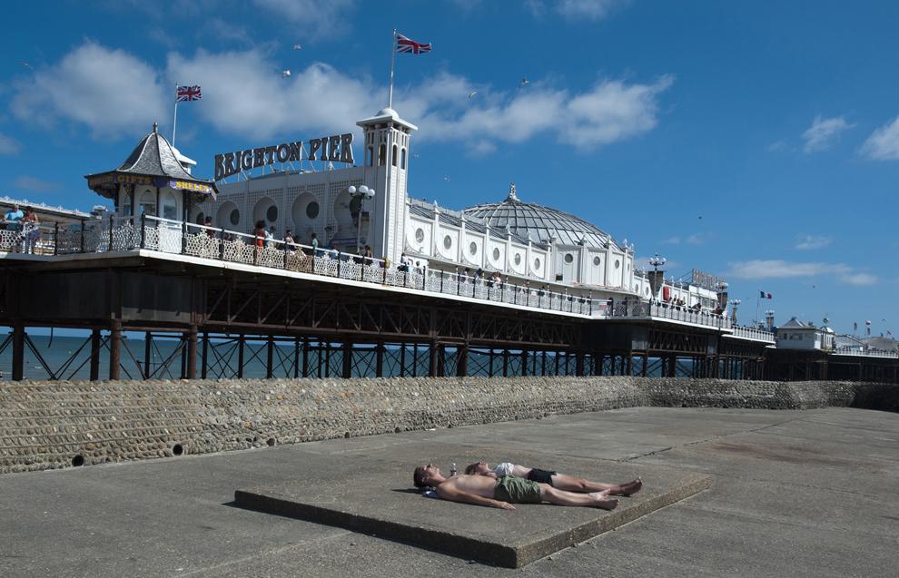 Două persoane fac plajă lângă Brighton Pier, pe coasta sudică a Marii Britanii, în Brighton, sâmbătă, 20 iulie 2013.