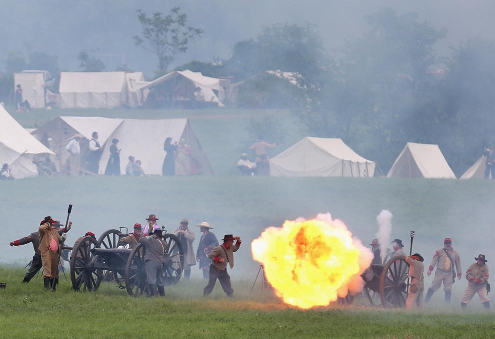 Participanţi la reconstituirea bătăliei de la Gettysburg din timpul Războiului Civil American, îmbrăcaţi în uniforme confederate, trag cu tunurile în direcţia forţelor unioniste, înaintea reconstituirii asaltului generalului Pickett, în ultima zi a evenimentului, în Gettysburg, Pennsylvania, Statele Unite, duminică, 30 iunie 2013.
