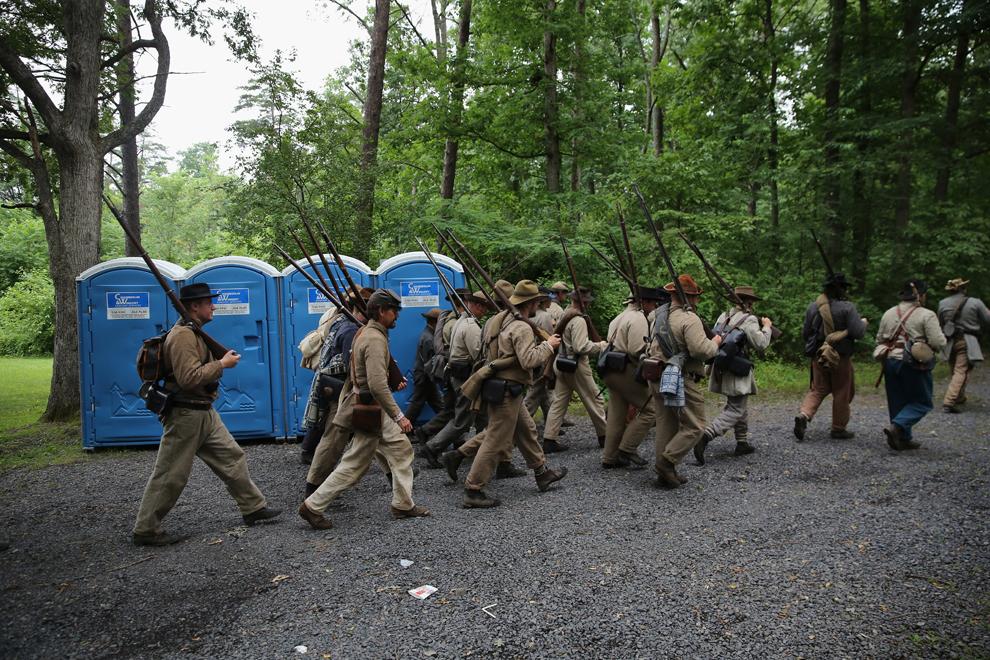 Participanţi la reconstituirea bătăliei de la Gettysburg din timpul Războiului Civil American, îmbrăcaţi în uniforme confederate, mărşăluiesc spre câmpul de luptă pentru a înscena un atac, în Gettysburg, Pennsylvania, Statele Unite, marţi, 2 iulie 2013.