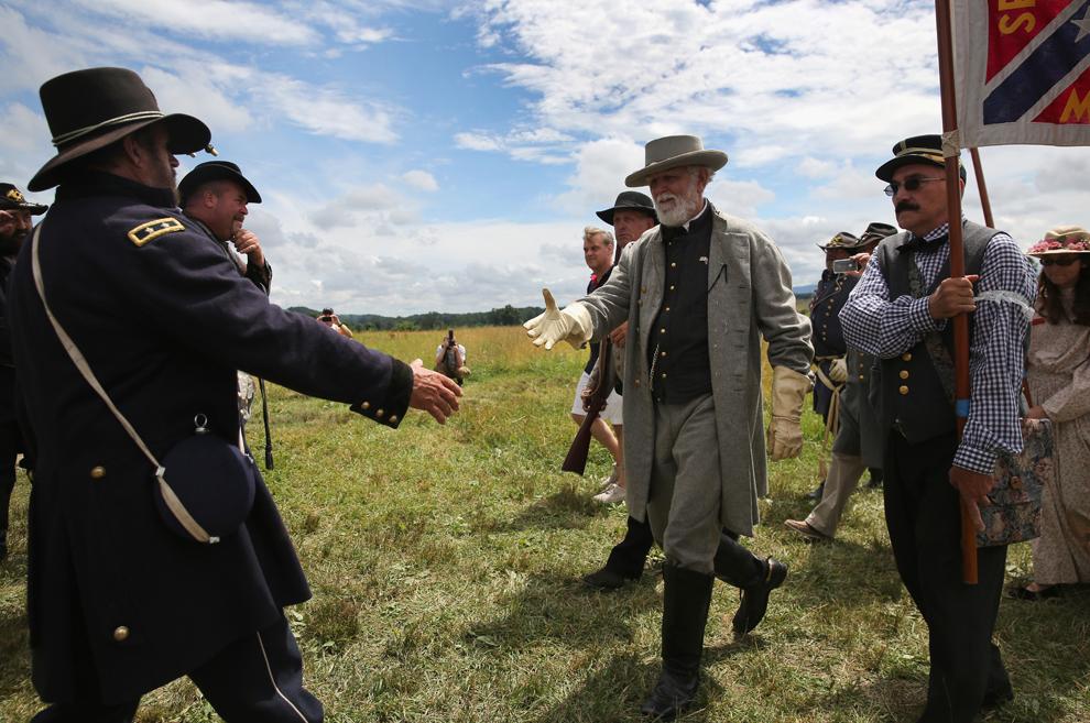 Un pasionat al reconstituirilor istorice care joacă rolul generalului confederat Robert E. Lee dă mâna cu un participant unionist, la finalul reconstituirii asaltului generalului Pickett din ultima zi a bătăliei de la Gettysburg din timpul Războiului Civil American, în Gettysburg, Pennsylvania, Statele Unite, marţi, 2 iulie 2013.