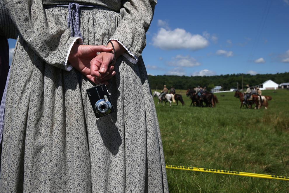 O femeie care participă la reconstituirea bătăliei de la Gettysburg din timpul Războiului Civil American ţine în mână un aparat de fotografiat, în Gettysburg, Pennsylvania, Statele Unite, sâmbătă, 29 iunie 2013.