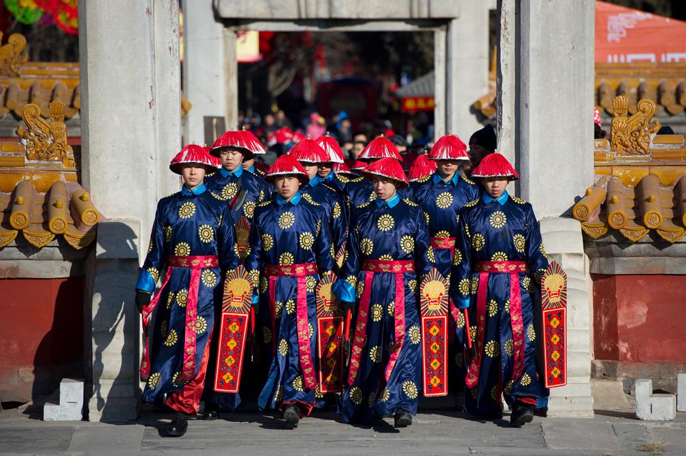 Mai mulţi actori îmbrăcaţi în costume din timpul dinastiei Qing participă la reconstituirea unei ceremonii tradiţionale în cadrul căreia împăraţii Chinei se rugau pentru noroc, în timpul deschiderii târgului anual din parcul Templului Pământului, în Beijing, duminică, 22 ianuarie 2012.