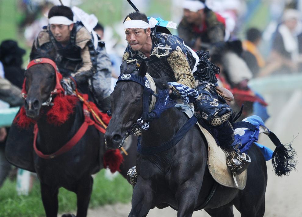 Localnici îmbrăcaţi în armuri de samurai călăresc în timpul festivalului anual Sano Nomaoi, în Minamisoma, prefectura Fukushima, Japonia, duminică, 29 iulie 2012.