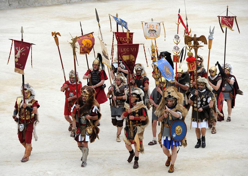 Mai mulţi bărbaţi purtând îmbrăcăminte militară din perioada Romei antice prezintă spectacolul Great Roman Games, în amfiteatrul din Nimes, în sudul Franţei, sâmbătă, 28 aprilie 2012. Evenimentul este o evocare istorică a jocurilor din amfiteatru, aşa cum ar fi arătat ele in anul 122 e.n.